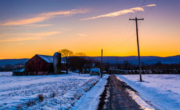 Barn and snow covered fields along a country road in rural Frede Stock Image