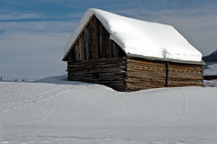 Barn in snow field. Snow covered hill with buildings Stock Image