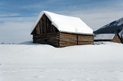Barn in snow field. Snow covered hill with buildings Stock Photography