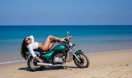Barn som är sexuellt, flickan på motorcykeln, på en strand Fotografering för Bildbyråer