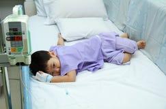 Barn som är tålmodiga i sjukhussäng Arkivbild