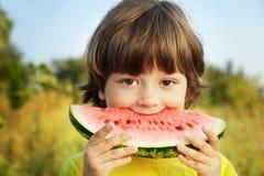 barn som äter den lyckliga vattenmelonen Royaltyfria Bilder