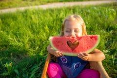 barn som äter den lyckliga vattenmelonen royaltyfria foton