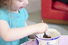 Barn som äter flickan för ung unge för kaka för choklad för sötsakpuddingöken med skeden och den sjukliga maträtten arkivfoto