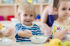Barn som äter från plattor i daghem Arkivbild