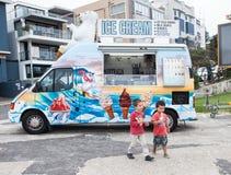 Barn som äter glass nära en icereamlastbil Arkivfoto