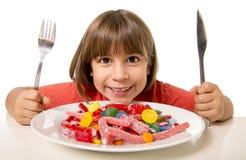 Barn som äter godisen som galet i sockermissbruk och sjukligt sött näringbegrepp royaltyfria foton