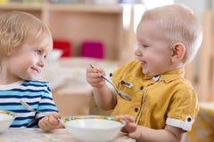 Barn som äter i dagis royaltyfria bilder