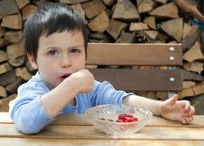 Barn som äter jordgubbar Arkivbild