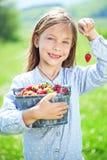 Barn som äter jordgubbar i ett fält arkivfoto
