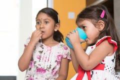 Barn som äter och dricker arkivfoto