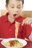 barn som äter spagetti royaltyfri foto