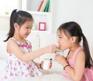 Barn som äter yoghurt royaltyfri bild