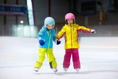 Barn som åker skridskor på inomhus isisbana Ungar och sund vintersport för familj Pojke och flicka med isskridskor Aktiv efter sk royaltyfria bilder