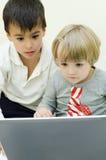 Barn som använder bärbara datorn Arkivbilder