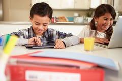 Barn som använder bärbara datorn och den Digital minnestavlan för att göra läxa arkivbild