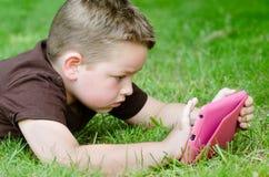 Barn som använder minnestavladatoren arkivbild