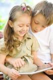 Barn som använder minnestavladatoren Royaltyfri Fotografi