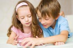 Barn som använder minnestavladatoren Arkivfoto
