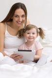 Barn som använder minnestavlan med hennes moder arkivbild
