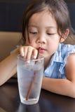 Barn som använder sugrör för att dricka vatten från exponeringsglas Arkivbild