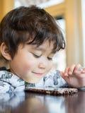 Barn som använder smartphonen Arkivbild
