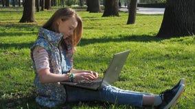 Barn som arbetar på bärbara datorn i natur En tonårs- flicka som bär solglasögon, sitter på gräset i parkera Solig utomhus- dag f lager videofilmer