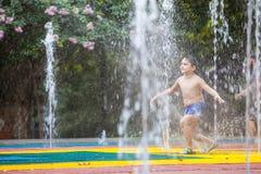 Barn som av offentligt kyler springbrunnen Arkivbilder