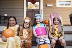 Barn som bär allhelgonaaftondräkter för trick eller behandling royaltyfria foton