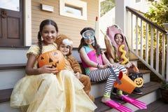 Barn som bär allhelgonaaftondräkter för trick eller behandling arkivfoto