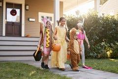 Barn som bär allhelgonaaftondräkter för trick eller behandling arkivbild