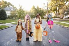 Barn som bär allhelgonaaftondräkter för trick eller behandling arkivbilder