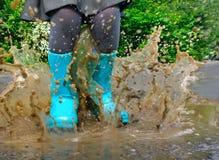 Barn som bär blåa regnkängor som hoppar in i en pöl Royaltyfria Foton