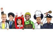 Barn som bär framtida Job Uniforms Royaltyfri Foto