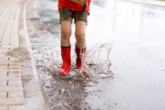 Barn som bär röda regnkängor som hoppar in i en pöl Royaltyfri Fotografi