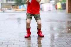 Barn som bär röda regnkängor som hoppar in i en pöl Fotografering för Bildbyråer