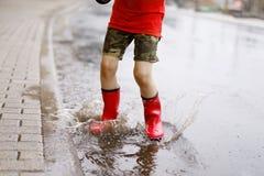 Barn som bär röda regnkängor som hoppar in i en pöl Royaltyfri Foto