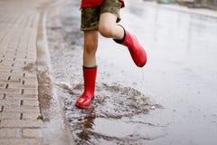 Barn som bär röda regnkängor som hoppar in i en pöl Royaltyfri Bild
