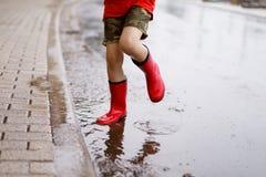 Barn som bär röda regnkängor som hoppar in i en pöl Arkivbild