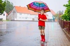 Barn som bär röda regnkängor som hoppar in i en pöl close upp Unge som har gyckel med att plaska med vatten Varm skurkroll arkivbilder