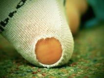 Barn som bär smutsiga sockor med hål i hälet Ben på grön matta Royaltyfri Bild