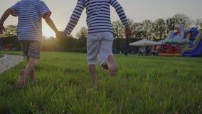 Barn som barfota kör över gräsmattan Roligt utomhus stock video