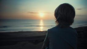 Barn som beundrar härlig solnedgång på kust stock video