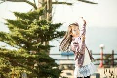 Barn som blåser en maskros i en parkera Arkivfoto