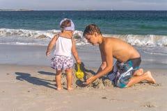 Barn som bygger en sandslott royaltyfri fotografi