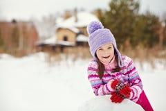 Barn som bygger en snögubbe fotografering för bildbyråer