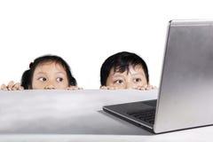 Barn som döljer bak den vita tabellen royaltyfria foton