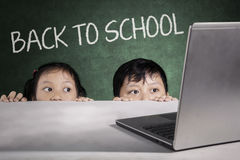 Barn som döljer med tillbaka till skolatext ombord Royaltyfria Foton