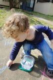 Barn som drar med krita utanför Arkivbild