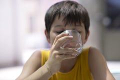 Barn som dricker ett exponeringsglas av rent vatten arkivbild